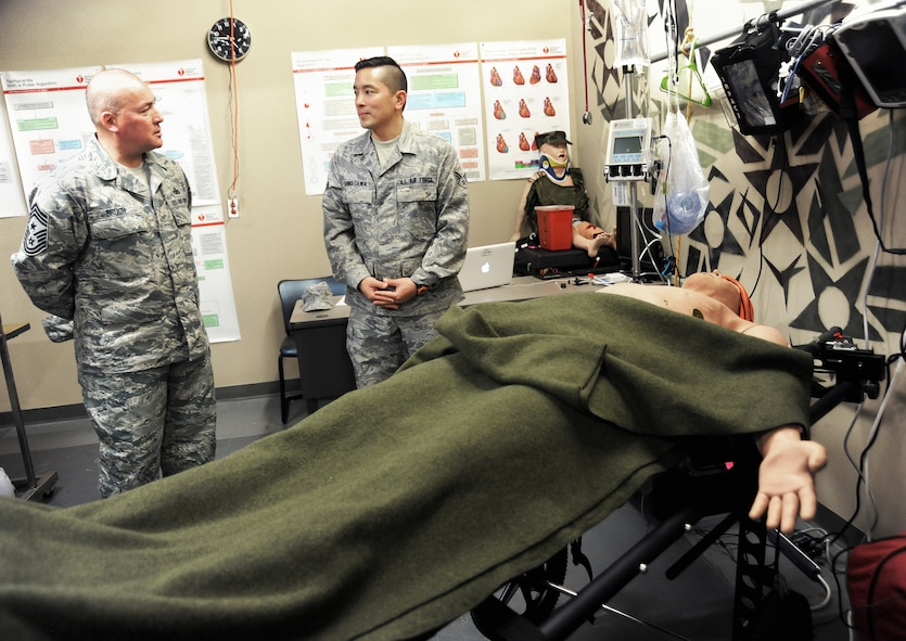 Oregon National Guard Senior Airman Korey Shinagawa, a medic assigned to the 142nd Fighter Wing Medical Group, right, gives a briefing to Chief Master Sgt. Mitchell O. Brush, Senior Enlisted Advisor for the National Guard Bureau, left, during his tour of the Portland Air National Guard Base, Ore., Jan. 5, 2015. Shinagawa discussed training techniques used by members of the Oregon National Guard's CERFP (CBRNE Enhanced Response Force Package) to Chief Brush as he took time to meet Airmen appointed to the highly trained medical team. (U.S. Air National Guard photo by Tech. Sgt. John Hughel, 142nd Fighter Wing Public Affairs/Released)