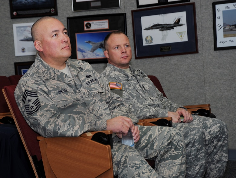 Chief Master Sgt. Mitchell O. Brush, Senior Enlisted Advisor for the National Guard Bureau, left, and SGM Shane Lake, Oregon National Guard Senior Enlisted Advisor, right, listen to remarks from senior enlisted leaders from the 142nd Fighter Wing during a briefing at the Portland Air National Guard Base, Ore., Jan. 5, 2015. Chief Brush toured the air base and led a town hall event to highlight the changes and challenges that Soldiers and Airmen of the National Guard face going into the New Year. (U.S. Air National Guard photo by Tech. Sgt. John Hughel, 142nd Fighter Wing Public Affairs/Released)