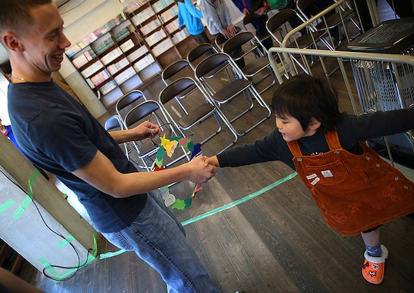 Cpl. Ruben Salinas, a resident Marine Air Ground Task Force planner for Marine Aircraft Grounp12 aboard Marine Corps Air Iwakuni, Japan, shakes hands with a young child after receiving a handmade Christmas ornament while visiting the Akebono Orphanage in Nasake Sima, Yamaguti, Japan, on Dec. 23, 2014.  As a part of giving back to the Japanese locals, Marine Aircraft Group 12 Marines collected 777 cans of food from their unit holiday party to distribute to those in need.