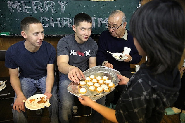 Cpl. Ruben Salinas, left, a resident Marine Air Ground Task Force planner for Marine Aircraft Group 12 aboard Marine Corps Air Station Iwakuni and Cpl. Matthew Ahn, right, a chemical, biological, radiological and nuclear defense specialist with MAG-12, eat finger food made by the children from the Akebono Orphanage in Nasake Sima, Yamaguti, Japan, Dec. 23, 2014. As a part of giving back to the Japanese locals, MAG-12 Marines collected 777 cans of food from their unit holiday party to distribute to those in need. Four hundred of those cans went to the children's home that day.