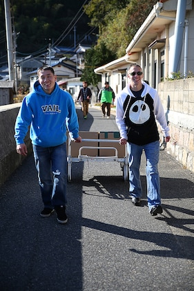 Cpl. Matthew Ahn, left, a chemical, biological, radiological and nuclear defense specialist aboard Marine Corps Air Station Iwakuni, and Cpl. Ruben Salinas, right, resident Marine Air Ground Task Force planner for Marine Aircraft Group 12, walk with their boxes of canned food to the Akebono Orphanage in Nasake Sima, Yamaguti, Japan, Dec. 23, 2014. As a part of giving back to the Japanese locals, MAG-12 Marines collected 777 cans of food from their unit holiday party to distribute to those in need.