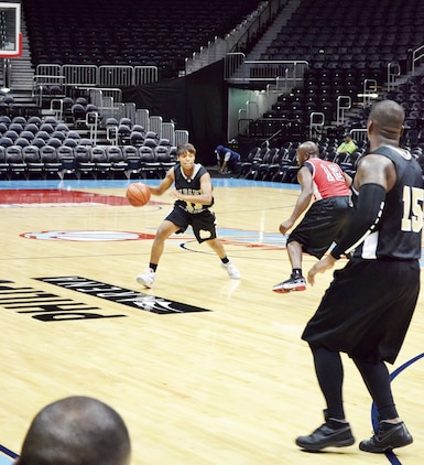 Sgt. Candice Clark-Thomas dribbles down the court while playing on Marine Corps Logistics Base Albany's basketball team in Phillips Arena, Atlanta, Ga., recently.