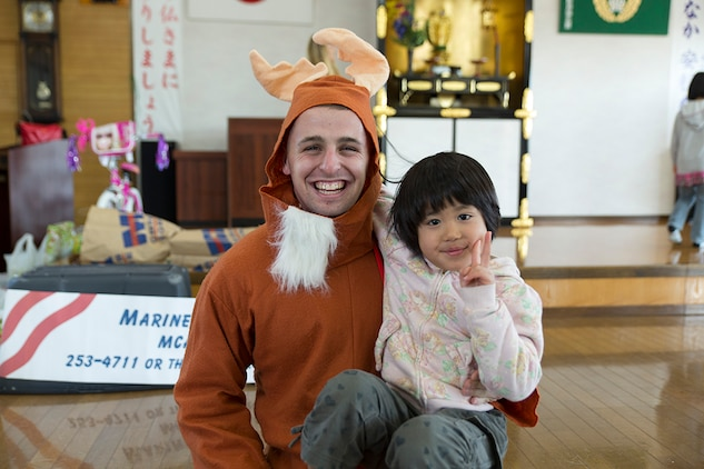 A volunteer from Marine Corps Air Station Iwakuni, Japan, poses with a child during a visit to a children's home in Hofu, Japan, Dec. 23, 2014. The Marine Thrift Store hosted the visit after collecting toys during a toy drive and motorcycle rally earlier this year. The rally collected more than 300 toys to give to the children's home.