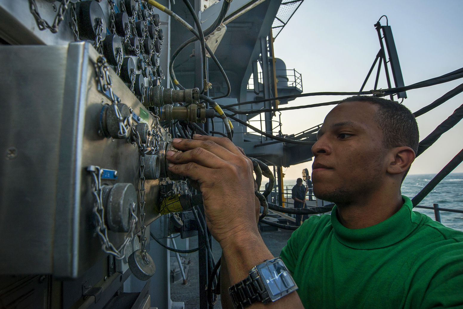 us navy petty officer steve smith connects cables on the fantail of the aircraft carrier uss