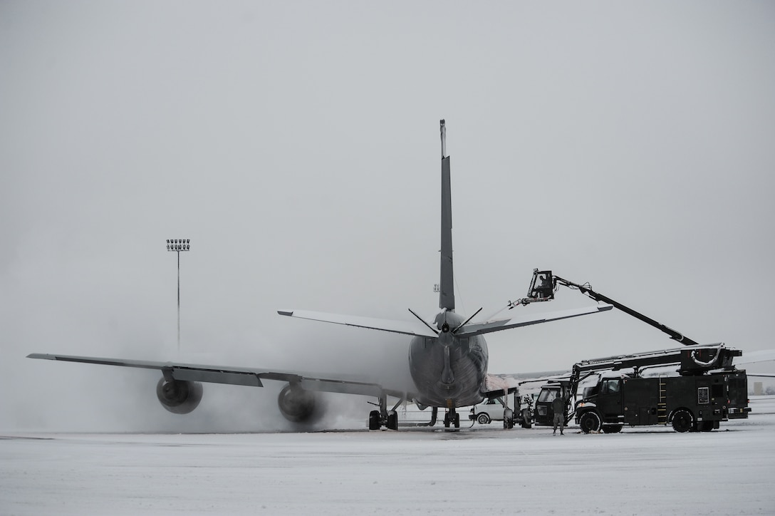 Airmen from the 92nd Aircraft Maintenance Squadron work together to deice a KC-135 Stratotanker Jan. 29, 2014, at Fairchild Air Force Base, Wash. Aircraft deicing is a process in which liquid solutions are sprayed onto an aircraft during the winter to both defrost and prevent future precipitation from freezing. Snow and ice on the wings and rear tail component change their shape and disrupt the airflow making it difficult to fly and diminishes fuel economy. (U.S. Air Force photo/Staff Sgt. Alexandre Montes)