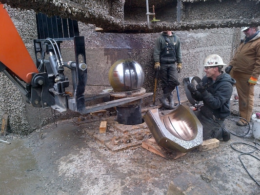 Illinois Waterway Maintenance Crew members, Craig Williams, Cory Bowen and Mark Hanson remove the pintle ball and bushing from the lower right sector gate at T.J. O'Brien Lock.