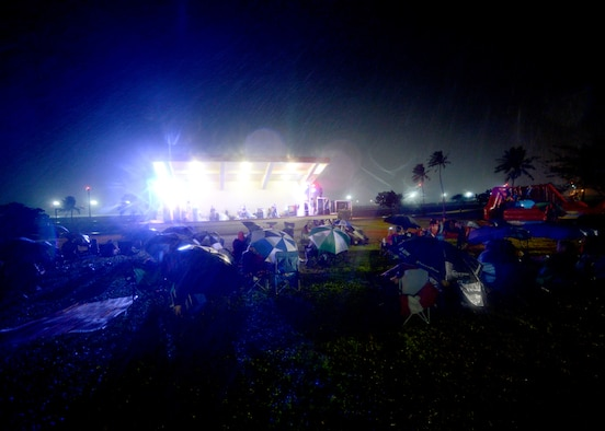 Team Andersen family members hunker down during a rainstorm while alternative rock band Vertical Horizon play on during a free concert Jan. 6, 2015, at the Arc Light Amphitheater at Andersen Air Force Base, Guam. Music fans braved constant rain and wind to hear the band play songs from their double platinum album, Everything You Want. (U.S. Air Force photo by Tech. Sgt. Zachary Wilson/Released.)