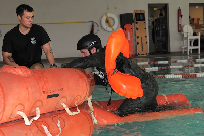 U.S. Air Force Tech. Sgt. Tony Fancher, 355th Operations Support Squadron survival, evasion, resistance and escape specialist, watches as Tech. Sgt. Brent Reynertson, 55th Electronic Combat Group evaluator and mission crew supervisor, boards a life raft during a water survival training refresher course at Davis-Monthan Air Force Base, Ariz., Jan. 5, 2015. This portion of the refresher course ensures aircrew members know how to properly enter a life raft without incident in order to preserve lives in the event of a ditched aircraft. (U.S. Air Force photo by Airman 1st Class Chris Drzazgowski/Released)