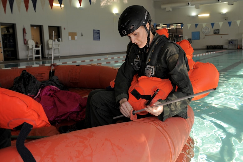 U.S. Air Force Staff Sgt. Whitni Levering, 42nd Electronic Combat Squadron airborne linguist, assembles canopy supports on a life raft during a water survival training refresher course at Davis-Monthan Air Force Base, Ariz., Jan. 5, 2015. When fully assembled, canopies help protect occupants of the life raft from the elements while at sea.  (U.S. Air Force photo by Airman 1st Class Chris Drzazgowski/Released)