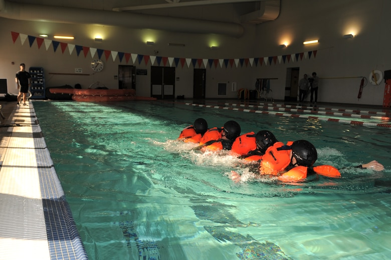 U.S. Air Force Airmen backstroke as a unit during a water survival training refresher course at Davis-Monthan Air Force Base, Ariz., Jan. 5, 2015. The group activity focused on getting aircrew members accustomed to working together while in water so they are able to preserve energy in the event of a ditched aircraft. (U.S. Air Force photo by Airman 1st Class Chris Drzazgowski/Released)