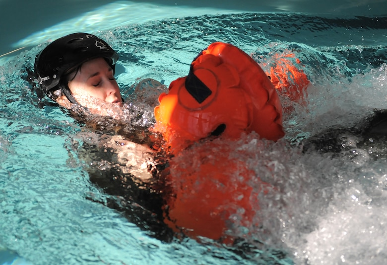 U.S. Air Force Staff Sgt. Whitni Levering, 42nd Electronic Combat Squadron airborne linguist, is dragged through the water by other Airmen during a water survival training refresher course at Davis-Monthan Air Force Base, Ariz., Jan. 5, 2015. The drag is intended to acclimate aircrew members to the similar sensations of landing in water with a deployed parachute. (U.S. Air Force photo by Airman 1st Class Chris Drzazgowski/Released)