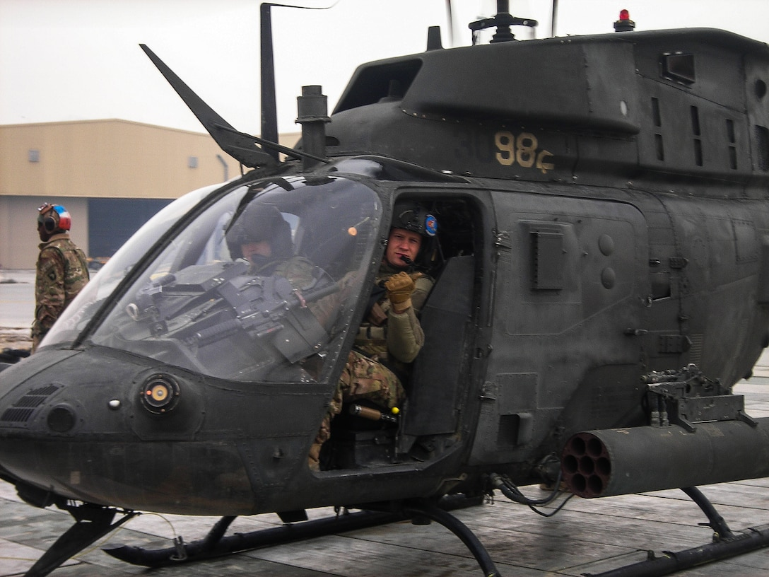 Master Sgt. Aaron Downing sits in a Bell OH-58 Kiowa helicopter in 2013 at Bagram Air Base, Afghanistan. Downing and his partner were conducting aerial reconnaissance of enemy crossing points. (Courtesy photo)