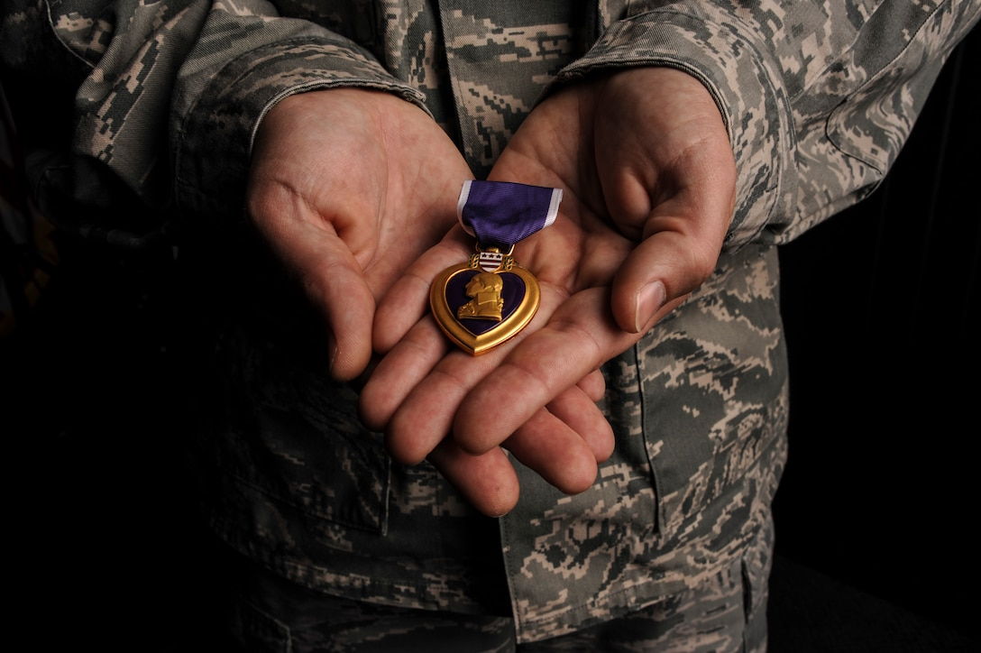 Master Sgt. Aaron Downing, a 19th Security Forces Squadron weapons and tactics superintendent displays his Purple Heart Dec. 10, 2014, at Little Rock Air Force Base, Ark. During his deployment to Iraq in 2007, Downing was wounded when his convoy was attacked by an improvised explosive device. (U.S. Air Force photo by Airman 1st Class Mercedes Muro)