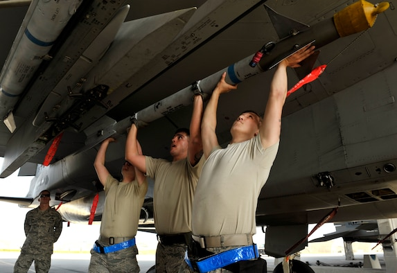 A weapons load crew team from the 44th Aircraft Maintenance Unit work together to lift an AIM-9 Sidewinder missile onto an LAU-128 Missile launcher Jan. 5, 2015, during a quarterly weapons load competition on Kadena Air Base, Japan. The competition tests teams' abilities to arm F-15 Eagles in a fast and safe manner. The competition was held between the 44th and 67th Aircraft Maintenance Units of the 18th Aircraft Maintenance Squadron. (U.S. Air Force photo/Naoto Anazawa)