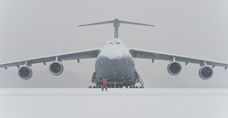 An aircraft maintainer stands on the flightline in front of a snow-covered C-5M Super Galaxy Jan. 6, 2015, at Dover Air Force Base, Del. Aircraft maintenance operations continued to keep the mission moving even though 1.4 inches of snow blanketed the flightline and aircraft. (U.S. Air Force photo/Roland Balik)