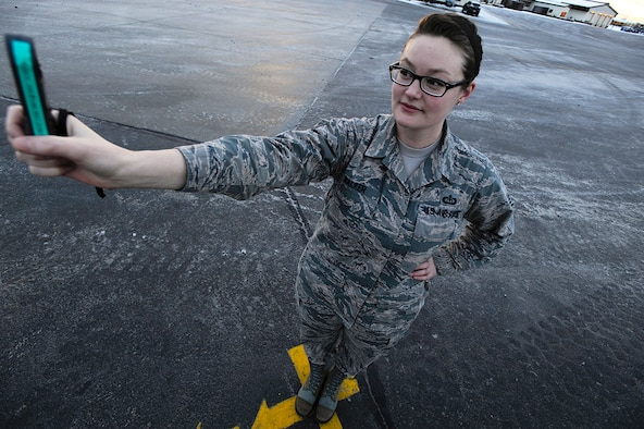Staff Sgt. Dana Walker uses a kestrel meter to gauge wind and temperature readings from the official observing location, the most unobstructed view of the airfield, painted on the runway at Joint Base Elmendorf-Richardson, Alaska, Dec. 28, 2014. Walker is a weather forecaster assigned to the 3rd Operations Support Squadron. (U.S. Air Force photo/Staff Sgt. Robert Barnett)