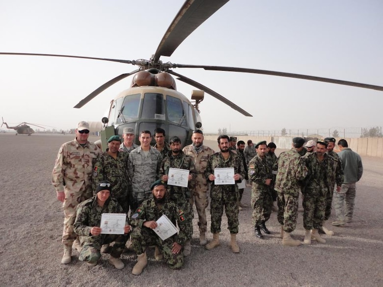 "Simon poses with first Afghan Air Force maintainers in 2011 after they received their 3-level upgrade at Shindand Air Force Base, Afghanistan. The maintainers, referred to as ""engine body mechanics,"" had to demonstrate competency of several core maintenance tasks to receive the upgrade. (U.S. Air Force photo)"