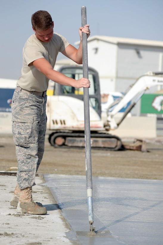 Airman 1st Class Joshua, Expeditionary Civil Engineer Squadron, works on a new concrete pad at the new Australian beddown site at an undisclosed location in Southwest Asia Oct. 30, 2014. Airmen with the ECES worked side-by-side with their Australian counterparts to construct 35 tents. (U.S. Air Force photo/Tech. Sgt. Marie Brown)