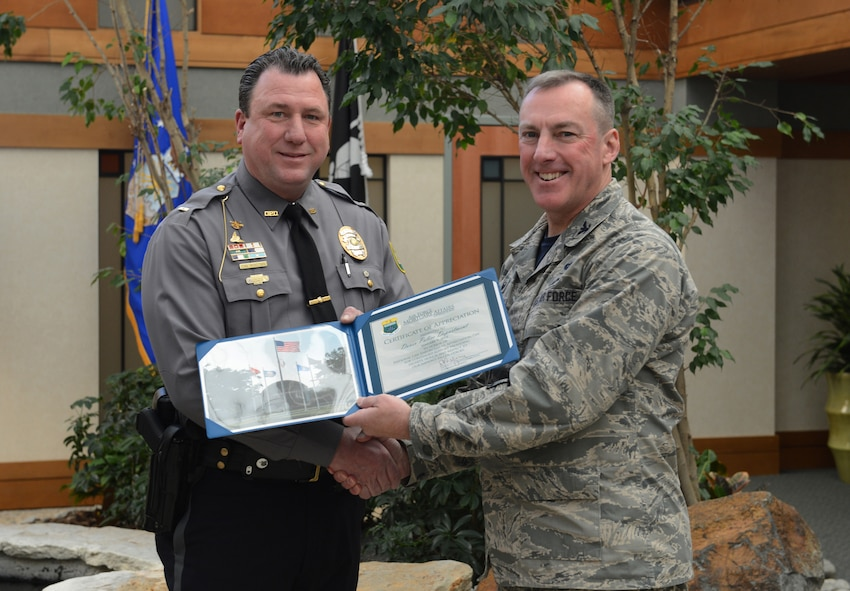 Col. Dan Merry, Air Force Mortuary Affairs Operations commander, presents a certificate of appreciation for the Dover Police Department to Lt. Dan McKeown Jan. 9, 2015, to recognize them for their support of the mortuary mission on National Law Enforcement Day. Several officers from the Dover Police Department assist as police escorts for fallen service members leaving the port mortuary. (U.S. Air Force photo/Staff Sgt. Nikoletta Kanakis)