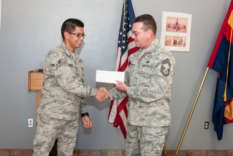 Airman 1st Class Israel Romero receives a check for $500 from Chief Master Sgt. Vandervort here January 5. (U.S. Air National Guard Photo by 2nd Lt. Lacey Roberts/Released)