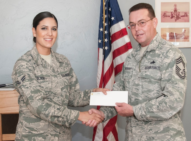 Airman 1st Class Jacqueline Ochoa receives a check for $500 from Chief Master Sgt. Vandervort here January 5. (U.S. Air National Guard Photo by 2nd Lt. Lacey Roberts/Released)