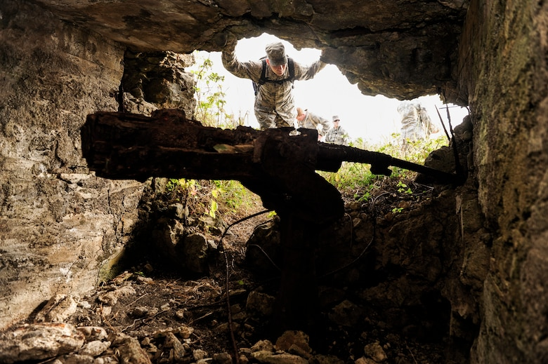 Airman 1st Class Jose Herrick, 18th Wing Judge Advocacy paralegal, peeks into the ruins of a Japanese bunker used during World War II, Jan. 8, 2015, on Iwo To, Japan. The U.S. Marine Corps led a 36-day assault on the island during the Battle of Iwo Jima. Japanese forces hid machinegun nests and other artillery weaponry to deter the invading Marines. (U.S. Air Force photo by Airman 1st Class John Linzmeier)