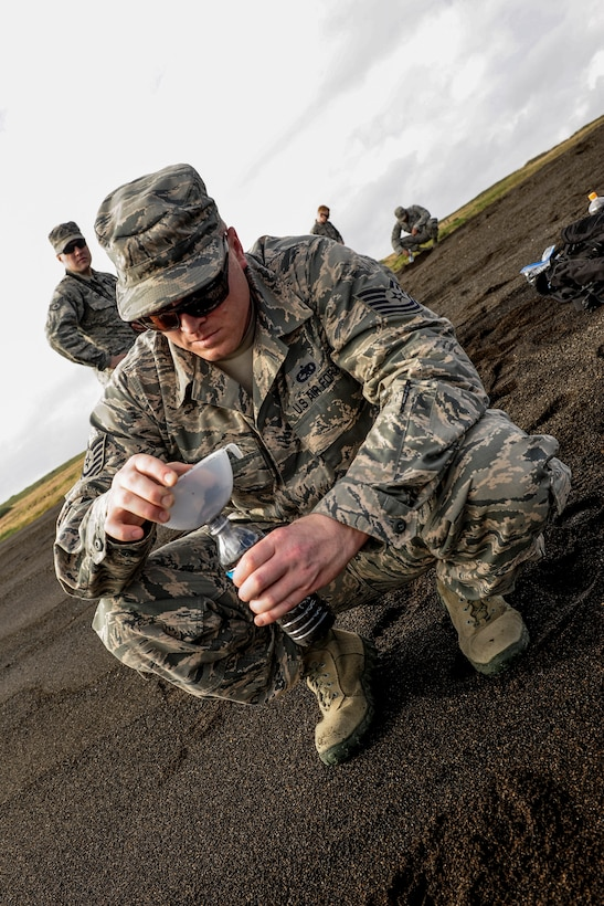 Tech. Sgt. Benjamin Weisensel, 733rd Air Mobility Squadron unit deployment manager, funnels sand into a bottle Jan. 8, 2015, on the shores of Iwo To, Japan. This is the location where thousands of Marines landed during the battle of Iwo Jima. (U.S. Air Force photo by Airman 1st Class John Linzmeier)