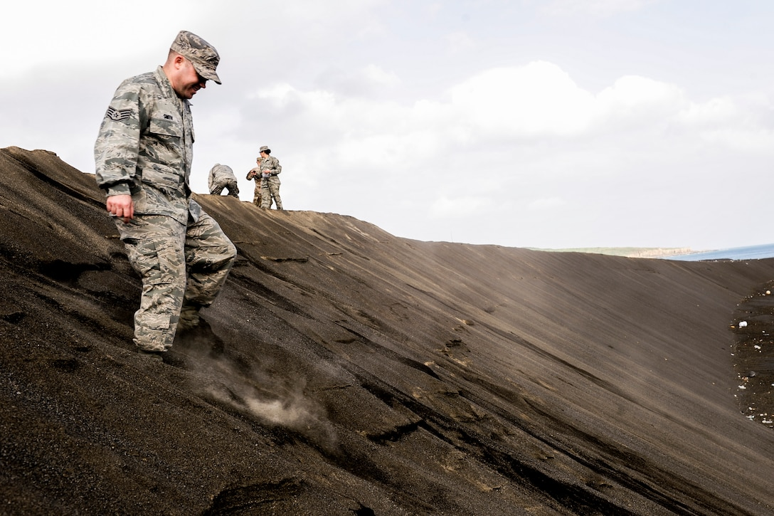 U.S. Air Force Staff Sgt. Corey Smith, 733rd Air Mobility Squadron air fright supervisor, treads down a slope of sand toward the coast Jan. 8, 2015 on Iwo To, Japan. Members of Kadena Air Base, Japan, gathered handfuls of sand to serve as a reminder of the battle of Iwo Jima, which had taken place on the island nearly 70 years ago. (U.S. Air Force photo by Airman 1st Class John Linzmeier)