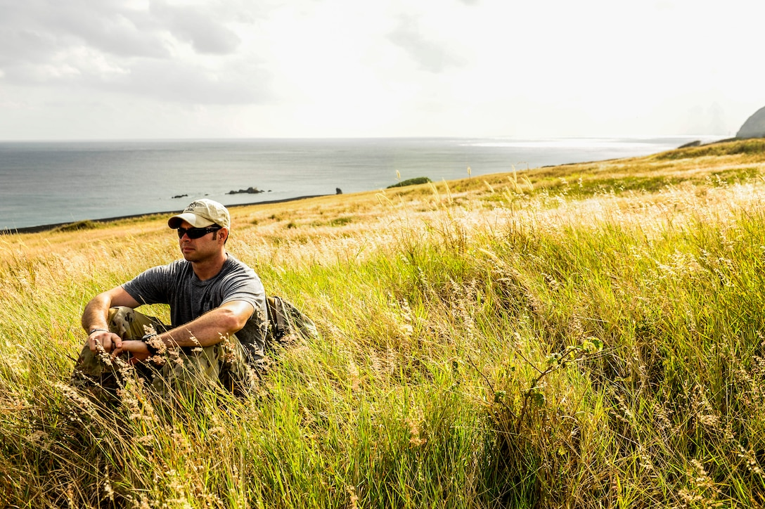 U.S. Air Force Staff Sgt. George Reed, 22nd Rescue Squadron pararescueman, sits near the coast Jan. 8, 2015, on Iwo To, Japan. The 18th Wing hosts a quarterly tour to the island, allowing a few Airmen to ride an aircraft during a training mission. Reed presided over the group of 32 Airmen as an emergency correspondent. The trip provided an opportunity to reflect on the sacrifices of the fallen fighters of the battle of Iwo Jima. (U.S. Air Force photo by Airman 1st Class John Linzmeier)