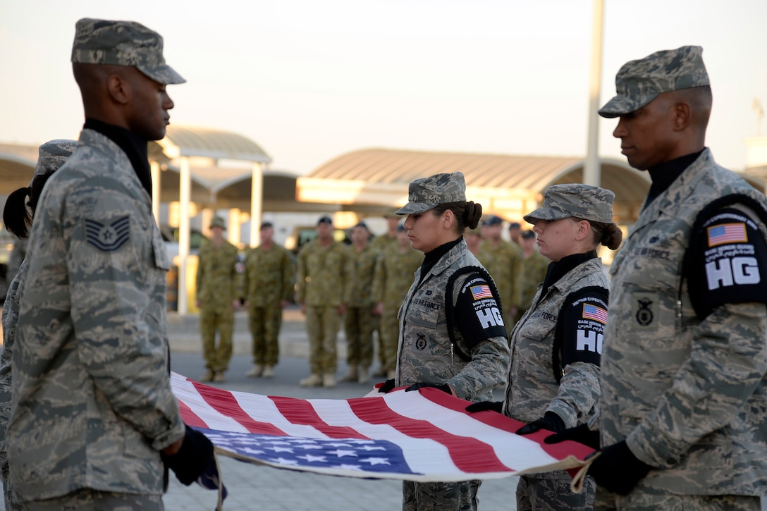 Members of the base honor guard prepare to fold the flag during the Veterans Day Retreat ceremony at an undisclosed location in Southwest Asia Nov. 11, 2014. Veterans Day is a time for everyone to come together to honor the men and women who have fought in America's military operations. (U.S. Air Force photo by Tech. Sgt. Marie Brown)