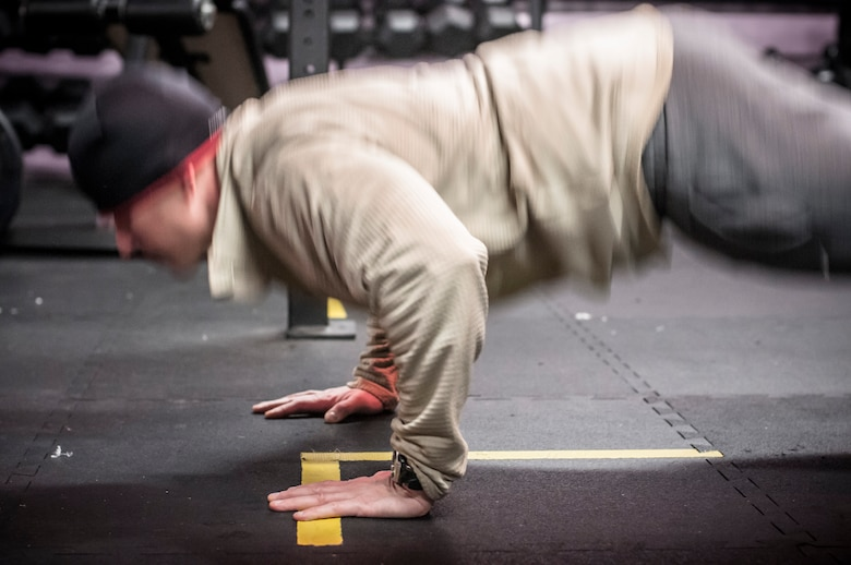 Capt. Daniel Curtin conducts burpees as part of a team crossfit workout. Both Airman from the 169th Air Support Operations Squadron, Peoria, IL, train together on a regular basis to maintain a high fitness requirement there career field requires on January 10, 2015. As Joint Terminal Attack Controllers the demanding job needs each airman to perform at peak performance alongside their Army counterparts out in the field. Besides the fitness benefits the members are getting teamwork, camaraderie and morale building are big advantages they are creating. They are building physical strength but more importantly the strength of teamwork to take to the battlefield. (U.S. Air National Guard photo by Master Sgt. Scott Thompson/released)