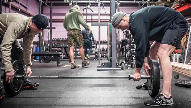 Capt. Daniel Curtin (left) and Staff Sgt. Nicholas Menzto switch out more weight prior to another repetition of the overhead squat. Both Airman from the 169th Air Support Operations Squadron, Peoria, IL, train together on a regular basis to maintain a high fitness requirement there career field requires on January 10, 2015. As Joint Terminal Attack Controllers the demanding job needs each airman to perform at peak performance alongside their Army counterparts out in the field. Besides the fitness benefits the members are getting teamwork, camaraderie and morale building are big advantages they are creating. They are building physical strength but more importantly the strength of teamwork to take to the battlefield. (U.S. Air National Guard photo by Master Sgt. Scott Thompson/released)