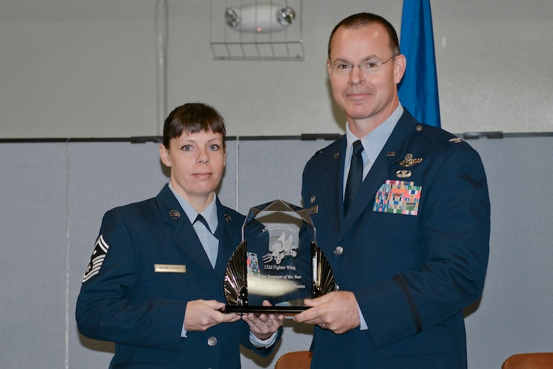 Col. Kevin Heer (right), Commander, 132nd Fighter Wing (132FW), Des Moines, Iowa, presents Senior Master Sgt. Kimberly McWilliams (left) with the 132FW First Sergeant of the Year award at the 2014 Annual Awards Ceremony held at the Valley Community Center, West Des Moines, Iowa on Saturday, November 1, 2014.  Senior Master Sgt. McWilliams has since been selected as the 2015 Iowa ANG Outstanding First Sergeant of the Year.  (U.S. Air National Guard photo by Staff Sgt. Linda K. Burger/Released)