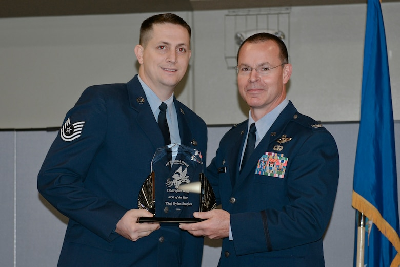 Col. Kevin Heer (right), Commander, 132nd Fighter Wing (132FW), Des Moines, Iowa, presents Tech. Sgt. Dylan Staples (left) with the 132FW NCO of the Year award at the 2014 Annual Awards Ceremony held at the Valley Community Center, West Des Moines, Iowa on Saturday, November 1, 2014.  Tech. Sgt. Staples has since been selected as the 2015 Iowa ANG Outstanding NCO of the Year.  (U.S. Air National Guard photo by Staff Sgt. Linda K. Burger/Released)