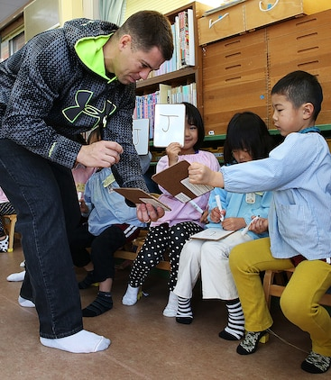Staff. Sgt. John Skehan, family readiness officer for Combat Logistics Company 36 aboard Marine Corps Air Station, Iwakuni, Japan, shows students of Kinnan Hoikuen in Iwakuni city, how to write out letters of the English alphabet during a community relations visit, Jan. 9, 2015. Marines from CLC-36 visited the school to teach basic English, interact with the Japanese children and play popular American games.