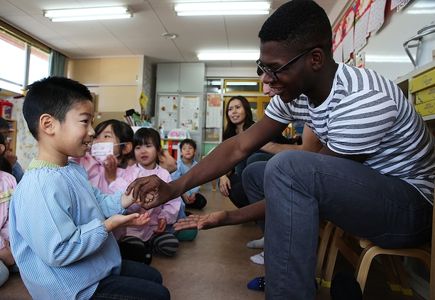 Lance Cpl. Khalil Miller, a mechanic with Combat Logistics Company 36 aboard Marine Corps Air Station, Iwakuni, Japan, plays rock-paper-scissors with a student from Kinnan Hoikuen in Iwakuni city during a community relations visit, Jan. 9, 2015. Marines from CLC-36 visited the school to teach basic English, interact with the Japanese children and play popular American games.