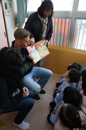 Lance Cpl. Cody Freeman, an electrician with Combat Logistics Company 36 aboard Marine Corps Air Station, Iwakuni, Japan, and a teacher from Kinnan Hoikuen in Iwakuni city, read English storybooks to students during a community relations visit, Jan. 9, 2015. Marines from CLC-36 visited the school to teach basic English, interact with the Japanese children and play popular American games. CLC-36's continual interaction with this school helps preserve an important bond between the Marines and local Japanese.