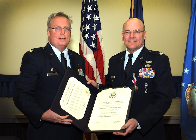 Lt. Col. John Quinn (left), 111th Medical Group commander, presents Lt. Col. (ret.) Preston Smith, former 111th Attack Wing medical administrative officer, with certificates for honorable service during a retirement ceremony held Jan. 10, 2015 at the wing headquarters building on Horsham Air Guard Station, Pa. Smtih's career spanned 39 years in both the active-duty Air Force and Air National Guard. (U.S. Air National Guard photo by Michael Shaffer/Released)
