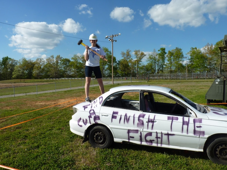 "Amber Wolfe, the daughter of AEDC employee Dee and Shawn Wolfe, prepares to smash cancer by damaging a car that represents cancer at the 2014 Relay For Life in Manchester. The ""Smashing Car"" is a fundraiser event for team REMEMBER at the relay. (Photo provided)"