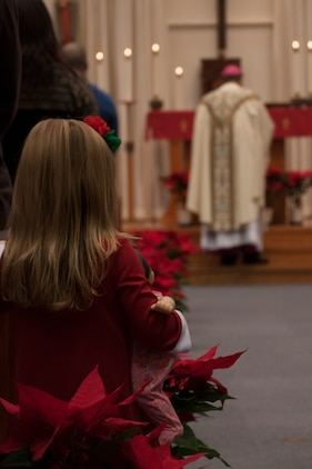 A child watches as Archbishop Timothy Broglio, Archbishop of the Military Services, USA, ascends the alter during a Roman Catholic mass inside the Marine Memorial Chapel aboard Marine Corps Air Station Iwakuni, Japan, Dec. 24, 2014. The Archdiocese of the Military Services, USA, was created by Pope John Paul II in 1985.