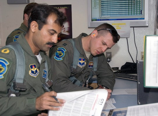 Pakistan Air Force Squadron Leader Azman Khalil, left, goes over flight information with Capt. Andy Wittke, an instructor pilot with the Arizona Air National Guard's 162nd Fighter Wing, before a training mission April 27, 2010. Khalil and seven other Pakistani pilots graduated from F-16C/D upgrade training at Tucson International Airport on May 4, 2010.