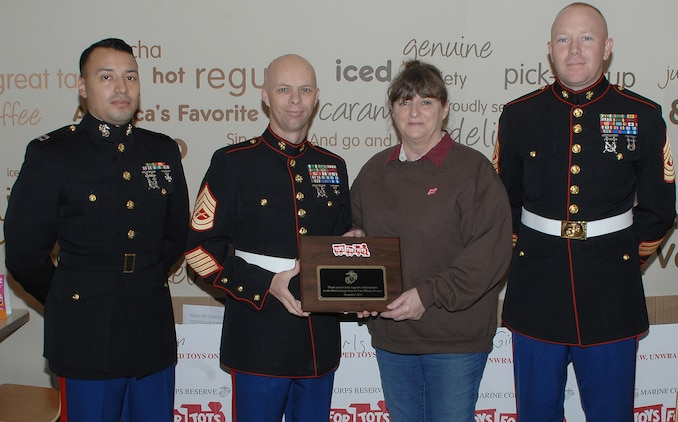 From left: Capt. Jose Castillo, I-I Inspector-Instructor; Gunnery Sgt. Johnny Ruby, coordinator, Toys for Tots; Teresa Salter, Dunkin Donuts multiunit manager, Albany and Thomasville, Ga., and 1st Sgt. James Britton, I-I first sergeant. Salter receives a plaque Tuesday from Ruby for her support during the Toys for Toys 2014 season. Dunkin Donuts supported the Toys for Tots team by donating donuts and coffee to more than 120 Marines during a two-week period.  According to Ruby, the day the toys were distributed, the Dunkin Donuts team showed how they cared about their community and wanted to give back by helping fill bags with toys.