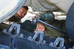 Cpl. Nick A. Buenviaje, left, tank gunner, and Sgt. Michelle A. Svec, tank crewman, both with Tank Platoon, Company B, Ground Combat Element Integrated Task Force, tighten a bolt on the track pad of an M1A1 Abrams tank during vehicle maintenance at Range SR-10, Marine Corps Base Camp Lejeune, North Carolina, Jan. 9, 2015. Marines with Tank Platoon conducted offensive and defensive engagements to prepare for an upcoming assessment at Marine Corps Air Ground Combat Center Twentynine Palms, California. From October 2014 to July 2015, the GCEITF will conduct individual and collective level skills training in designated ground combat arms occupational specialties in order to facilitate the standards based assessment of the physical performance of Marines in a simulated operating environment performing specific ground combat arms tasks. (U.S. Marine Corps photo by Sgt. Alicia R. Leaders/Released)