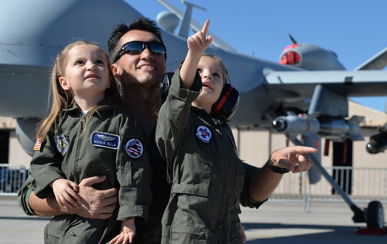 Natalie and Melanie watch the Legacy Bombers fly with their father Capt. Eric for the friends and family day at the 2014 Open House on Nellis Air Force Base, Nev., Nov. 7, 2014. The Open House is a two-day event that will depict the history of American aviation and salute recent accomplishments of America's military in operations around the globe through numerous military and civilian ground displays. (U.S. Air Force photo by Tech. Sgt. Nadine Barclay/Released) (Names withheld for security)