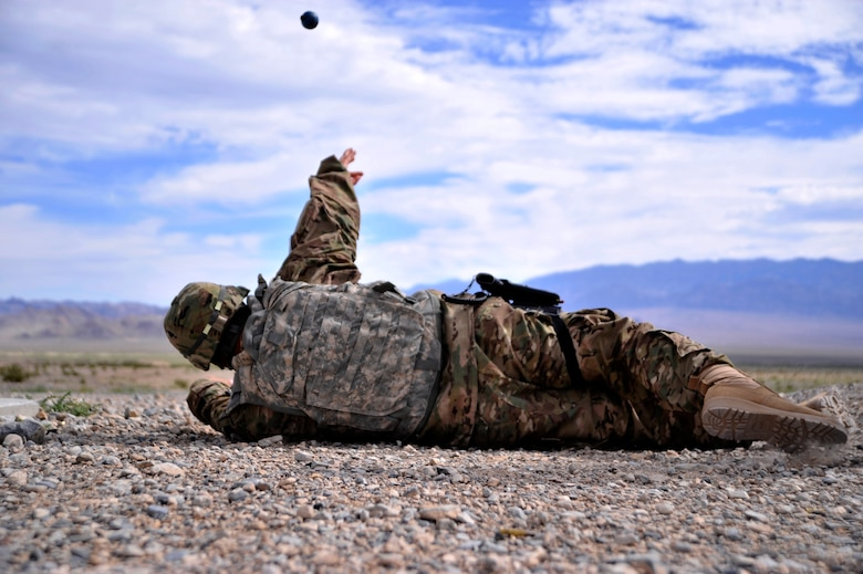 Staff Sgt. David Garcia, 99th Security Forces Squadron evaluator, throws an M-69 practice grenade during the last iteration of the M-67 fragmentation grenade training class Aug. 30, 2014, at Silver Flag Alpha, Nevada. Students completed this course as part of their pre-deployment training in case of an event that requires use of grenades. (U.S. Air Force photo by Airman 1st Class Christian Clausen/Released)