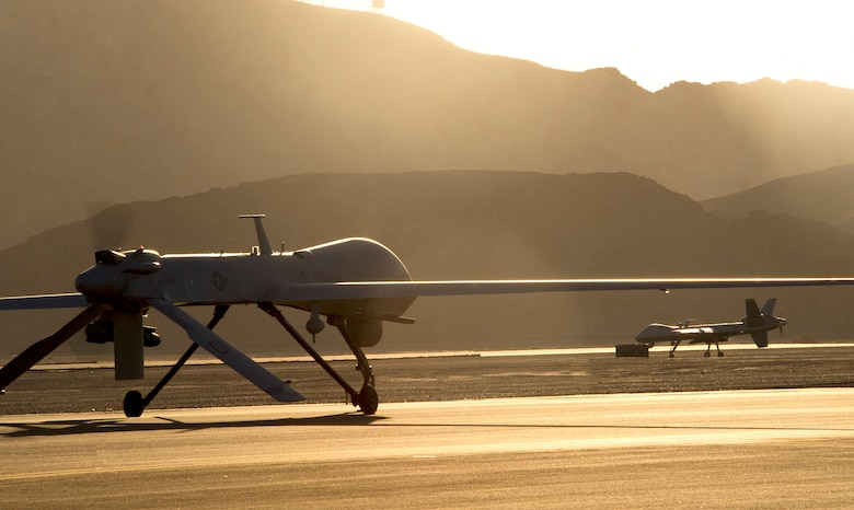 An MQ-1 Predator and MQ-9 Reaper taxi to the runway in preparation for take-off on Creech Air Force Base, Nev., June 13, 2014. The aircraft are flown under the 432nd Wing which trains pilots, sensor operators, and other remotely piloted aircraft crewmembers, and conducts combat surveillance and attack operations worldwide. (U.S. Air Force photo by Airman 1st Class Christian Clausen/Released)