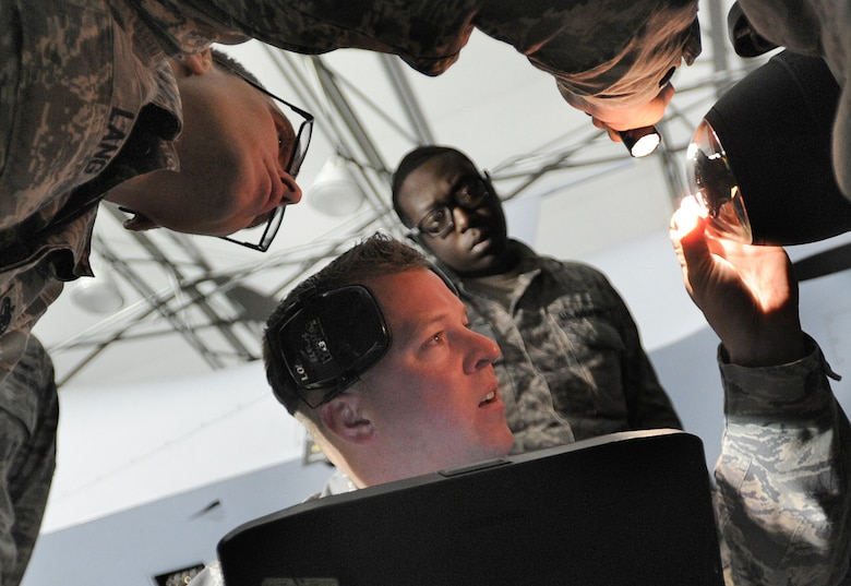 Airmen from the 432nd Aircraft Maintenance Squadron Tiger Aircraft Maintenance Unit weapons load crew inspect an AGM- 114 Hellfire missile loaded on an MQ-9 Reaper prior to launch at Creech Air Force Base, Nev., May 12, 2014. The 432nd Maintenance Group has continuously exceeded the RPA standard mission capable rate of 86 percent set by Air Combat Command through sound maintenance practices. Mission capable means the aircraft has no supply or maintenance issues preventing it from successfully completing a mission. (U.S. Air Force photo by Senior Master Sgt. Cecilio Ricardo/Released)