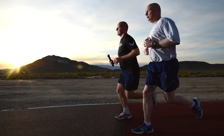 Chief Master Sgt. Paul Pohnert, left, 799th Air Base Squadron superintendent, and Master Sgt. Robert Livingston, 799th ABS first sergeant, participate in a 24-hour vigil run at Creech Air Force Base, Nev., during National Police Week May 16, 2014. Each runner carried a baton containing the names of 286 U.S. law enforcement officers who lost their lives during the past year. (U.S. Air Force photo by Tech. Sgt. Shad Eidson/Released)