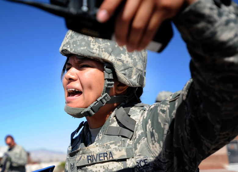 Staff Sgt. Liza Rivera, 799th Security Forces Squadron patrolman, yells to first responders during a simulated active shooter exercise at Creech Air Force Base, Nev., March 25, 2014. The scenario between Creech and Nellis Air Force Bases tested the emergency response capabilities of installation personnel, first responders and critical notification infrastructure. (U.S. Air Force photo by Senior Master Sgt. Cecilio Ricardo/Released)