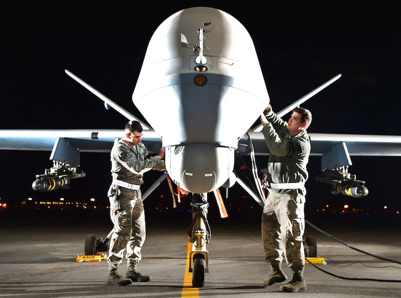 Airman 1st Class Steven, 432nd Aircraft Maintenance Squadron MQ-9 Reaper crew chief (left), and Airman 1st Class Taylor, 432nd Aircraft Maintenance Squadron MQ-9 Reaper crew chief (right), prepare an MQ-9 Reaper for flight during Combat Hammer May 15, 2014, Creech Air Force Base, Nev. Fighter, bomber and remotely piloted aircraft units around the Air Force are evaluated four times a year and provided weapons, airspace and targets from Hill AFB, Utah, or Eglin AFB, Fla. (U.S. Air Force photo by Staff Sgt. Nadine Barclay/Released)